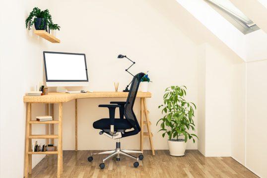 Arbeitsplatz unter der Dachschräge – Beispiel mit Nierenform Schreibtisch aus Holz mit Bürostuhl – Schreibtischlampe – Zimmerpflanze im weißen Blumentopf – Wandregal mit Pflanzen