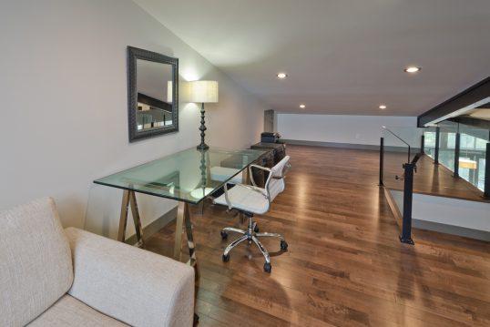 Modern eingerichtetes Arbeitszimmer im Dachgeschoss – Beispiel mit Glasschrei...