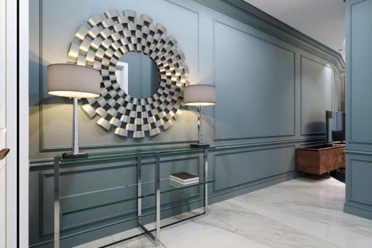 Idee für elegante Flureinrichtung im modernen Stil mit Dekoration - Beispiel mit Glasbeistelltisch  Tischlampen und runder Designspiegel - Wandgestaltung mit Paneelen in Blau