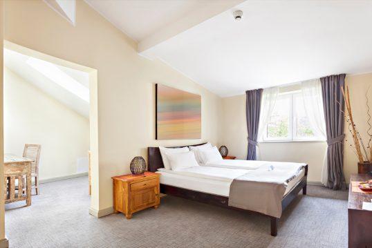 Gestaltungsidee für eine Ferienwohnung auf dem Dachboden – Schlafzimmer Beispiel mit Holzbett  Holznachtschrank mit Kerze & Bild über dem Bett – Vorhänge vor den Fenstern