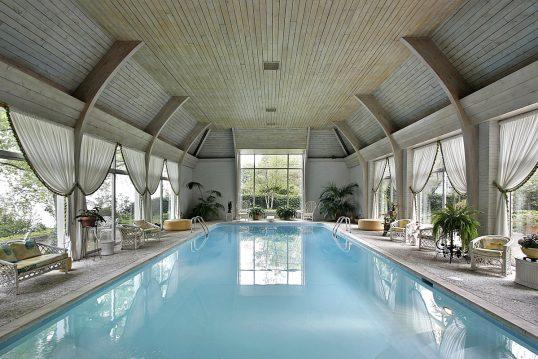 Schwimmbad Idee - Gemütliches Hallenbad mit Holzdach & Möbeln - Rattansofa & Korbstühle - Vorhänge als Deko & Sichtschutz vor den Fenstern