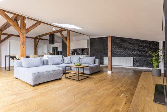 Wohnidee – Beispiel für ein geräumiges Wohnzimmer unter dem Dach im klassischen Stil mit grauem Sofa  Co...