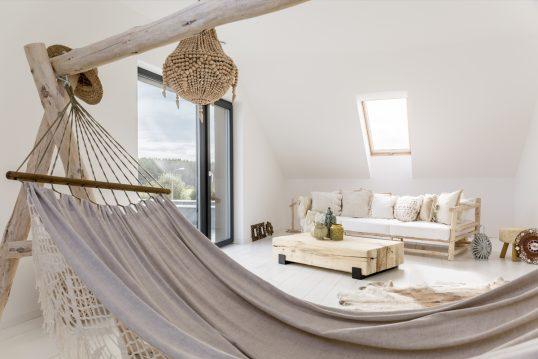 Gestaltungsidee für ein Jugendzimmer im Dach - Boho Style Dachzimmer mit Futonsofa & Holzbeistelltisch mit Dekovasen - Hängematte & Fellteppich