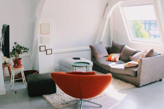 Wohnidee – Jugendzimmer unter dem Dach mit grauem Sofa  Drehsessel & eckigen Sitzkissen auf dem Teppich – verschiedene Beistelltische – Bilderrahmen an der weißen Wand