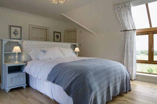 Gestaltungsidee für ein Landhaus Schlafzimmer in der Ferienwohnung – Beispiel mit großen Landhausbett mit integrierten Nachtschränken – weiße Nachttischlampen – Bilderrahmen als Dekoration