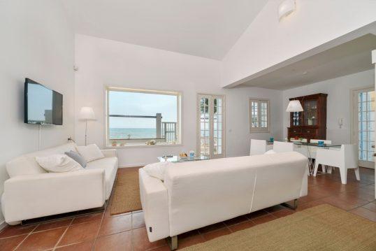 Mediterrane Ferienwohnung im Dach mit Ausblick aufs Meer - Einrichtungsidee mit weißen Ledersofas  Stehlampen & Essbereich mit Esstisch - Buffetschrank & Teppich