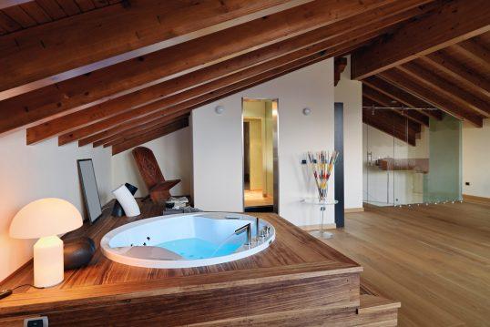 Wohnidee – Relaxbereich zu Hause unter dem Dach mit Whirlpool – Glasbeistelltisch mit Dekoration &...