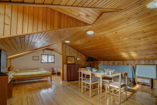 Rustikale Ferienwohnung Idee im Dach – Beispiel für ein Dachappartement mit Holzverkleidung – Essecke mit Sofa  Tisch & Stühlen – Schlafnische mit Einzelbetten