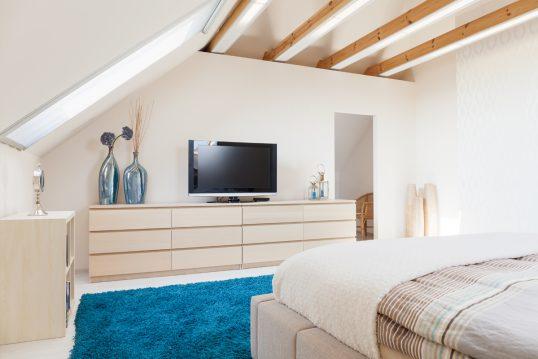 Einrichtungsbeispiel für ein modernes Schlafzimmer im Dachgeschoss – Idee für die Ferienwohnung oder Appartement – Großer Schrank mit Vasen & TV – Blauer Teppich vor dem Bett