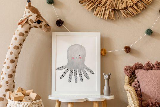 Babyzimmer oder Kinderzimmer Wandgestaltung Idee – Braune Wandfarbe mit Girlande – Bild in Bilderrahmen auf einem Beistelltisch – Korbsessel mit Kissen