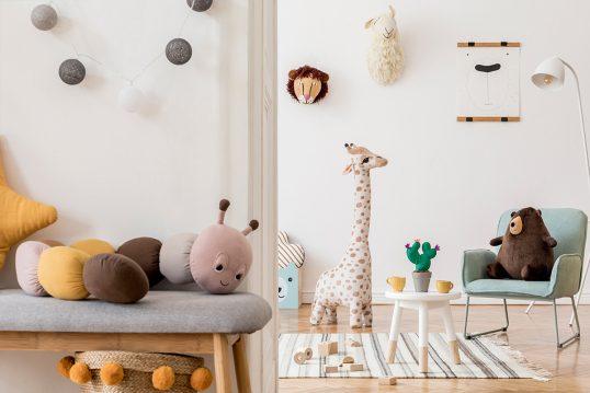 Skandinavische Kinderzimmer Idee mit Deko - Beispiel mit Polsterbank  gemütlichen Sessel & kleinen Beistelltisch - Lichterkette & Bild an der Wand - viele Plüschtiere als Dekoration