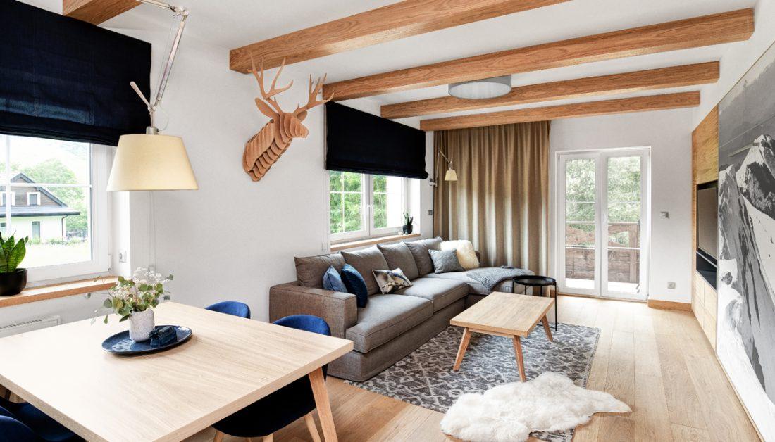 Landhaus Appartement Wohnung im modernen Landhausstil eingerichtet - Idee mit grauen Stoffsofa & Beistelltisch auf einem Teppich - Essbereich mit Esstisch & Schalenstühlen