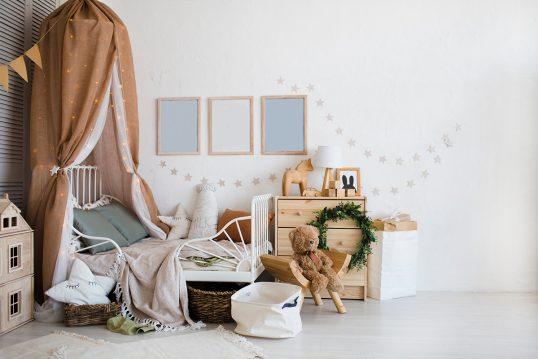 Kreative Kinderzimmereinrichtung mit Dekoration – Weißes Metallbett dekoriert mit Vorhang & Lichterkette – kleiner Schrank aus Holz – Wandgestaltung mit Bildern & Girlanden