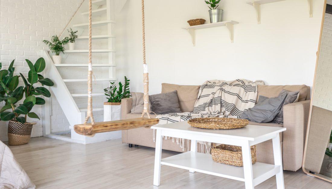 Wohnidee - Wohnzimmer Einrichtung im skandinavischen Landhausstil - Beispiel mit gemütlichen Sofa in beige & weißen Stauraum Couchtisch - Wandregale mit Dekoration