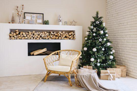 Wohnidee - Skandinavisches Kaminzimmer mit Weihnachtsdeko - Beispiel mit Korbstuhl vor dem Weihnachtsbaum - Weihnachtsfiguren