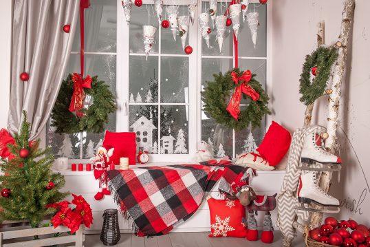 Wohnidee – Fenstergestaltung mit Weihnachtsdeko – Beispel mit geschmückten Fensterbrett mit Weihnachtsfiguren  Kerzen & Decke – Weihnachtsgirlande