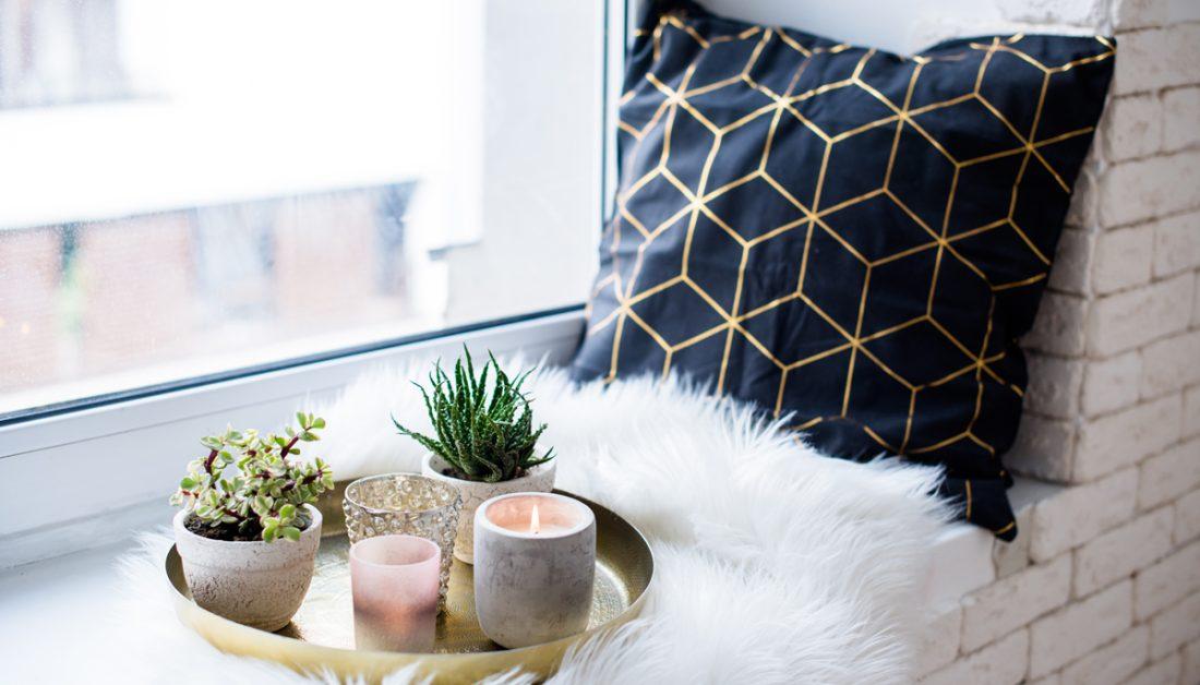 Wohnidee - Gemütliche Dekoration auf der Fensterbank mit goldenen Dekoteller - Teelichter & Pflanzen in Pflanzgefäßen - weißes Fell & Kissen