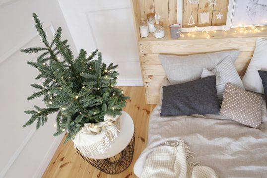 Weihnachtsdeko im skandinavischen Schlafzimmer – Künstlicher Weihnachtsbaum mit Lichterkette auf einem Metalltisch neben dem Holzbett – Bettablage mit Kerzen