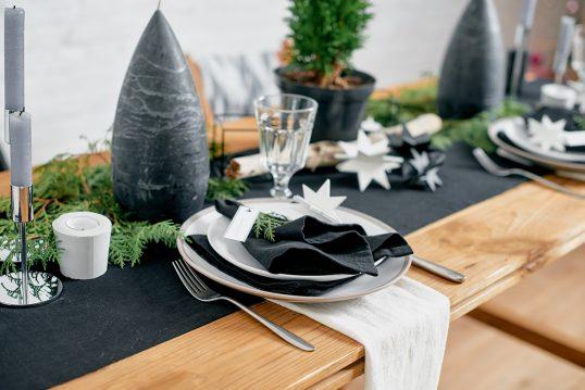 Beispiel mit einfacher weihnachtlicher Tischdeko – Idee mit dunklen Tischläufer  großer Kerze  Kerzenständer & Tannenzweigen auf dem Esstisch aus Holz