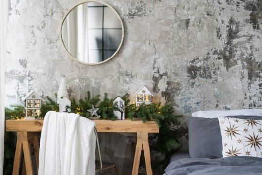 Einrichtungsidee mit Winterdeko – Schlafzimmer mit winterlich gestalteter Konsole aus Holz – Weihnachtsgirlande aus Tannenzweigen  Dekofiguren – Runder Spiegel  Stuhl & Bett
