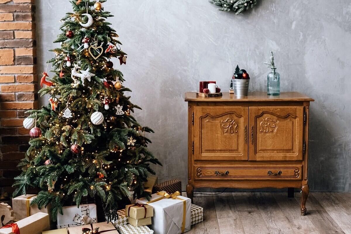 Bunt geschmückter Weihnachtsbaum neben kleiner Holzkommode
