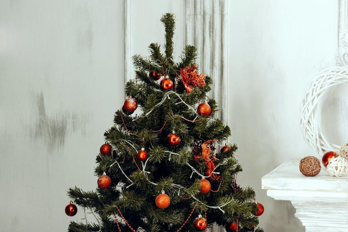 Künstlicher Weihnachtsbaum mit Lichterkette und roten Kugeln