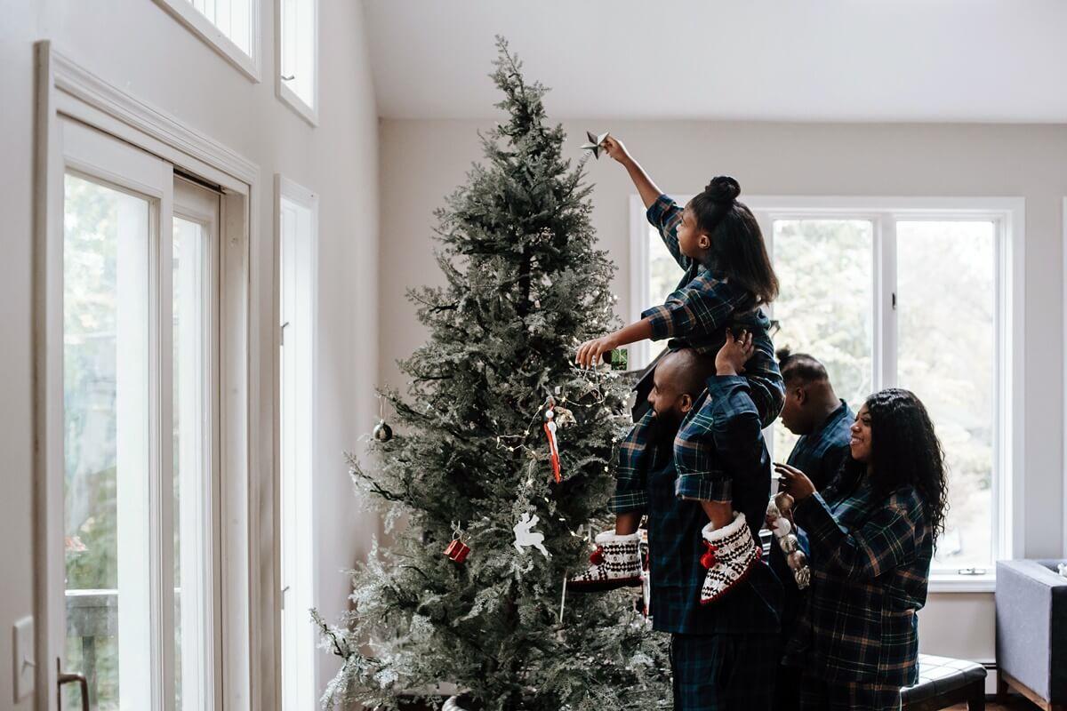 Familie schmückt gemeinsam ihren Weihnachtsbaum