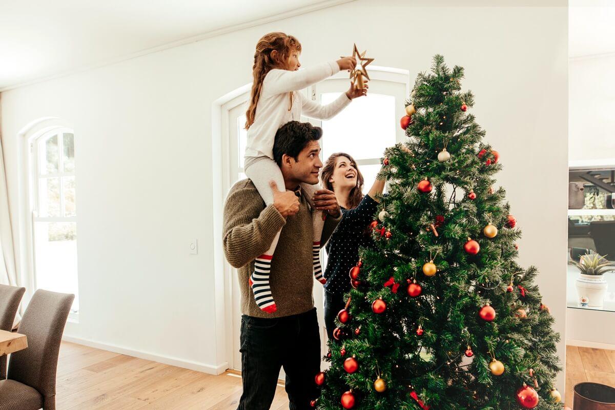 Familie setzt Weihnachtsstern auf die Spitze des Weihnachtsbaums