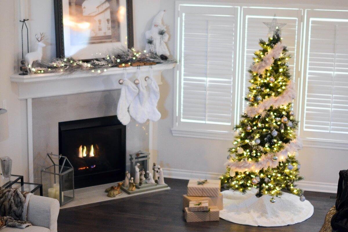 Weihnachtsbaum vor dem Kamin mit großer, weißer Weihnachtsdecke
