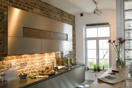 Einrichtungidee für die Küche - Designküche mit großen Wandschrank an einer rustikalen Wand - Schrankbeleuchtung & Deckenlampe - Tresentisch mit Vase & Blume