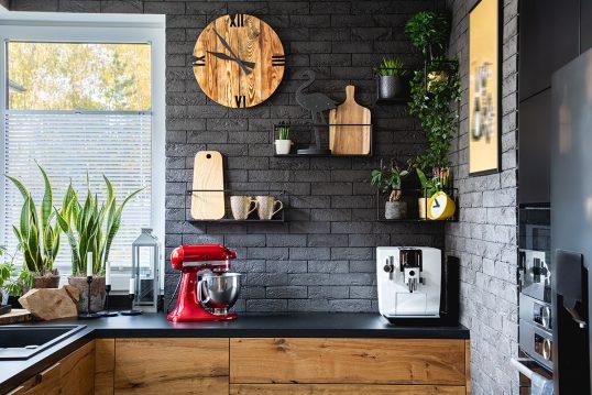 Wohnidee - Rustikale Küche mit dunkler Steinwand & Wandgestaltung - schwarze Wandregale aus Metall - Küchenuhr aus Holz & Küchendekoration